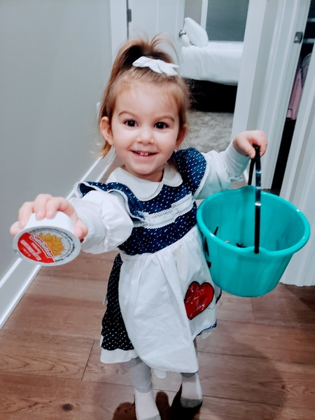Aria shows off her teal pumpkin bucket and a cup of sunflower butter donated for the Spooktacular event.
