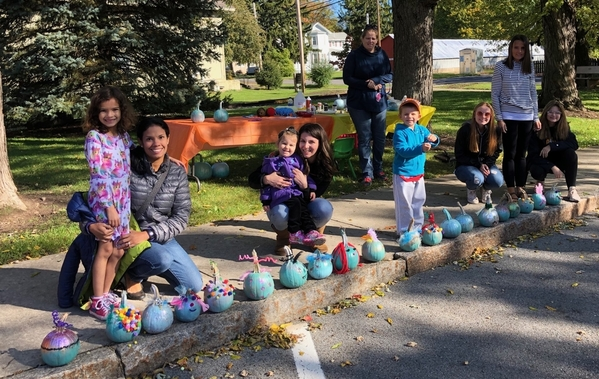 Stasi, Aria (middle) and other families show off the teal pumpkins they decorated at the Clifton Springs Library event.