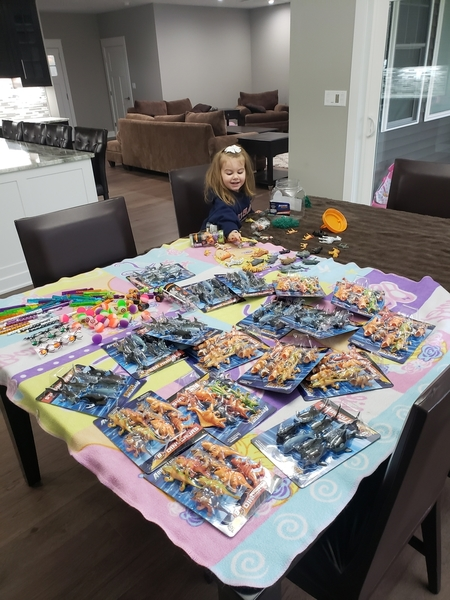 Aria helps her mom, Stasi, sort toy donations.